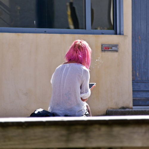 Rear view of woman using smart phone while sitting on bench