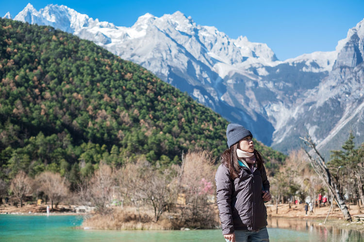 Woman wearing backpack while standing against mountains during winter