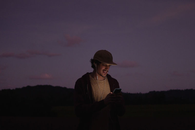 Man using smartphone while standing on field against sky during sunset