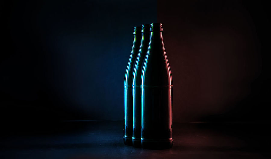 Close-up of glass bottle on table against black background