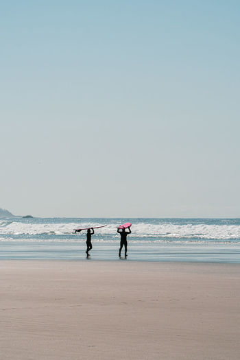 Silhouette couple walking on beach with surfboard