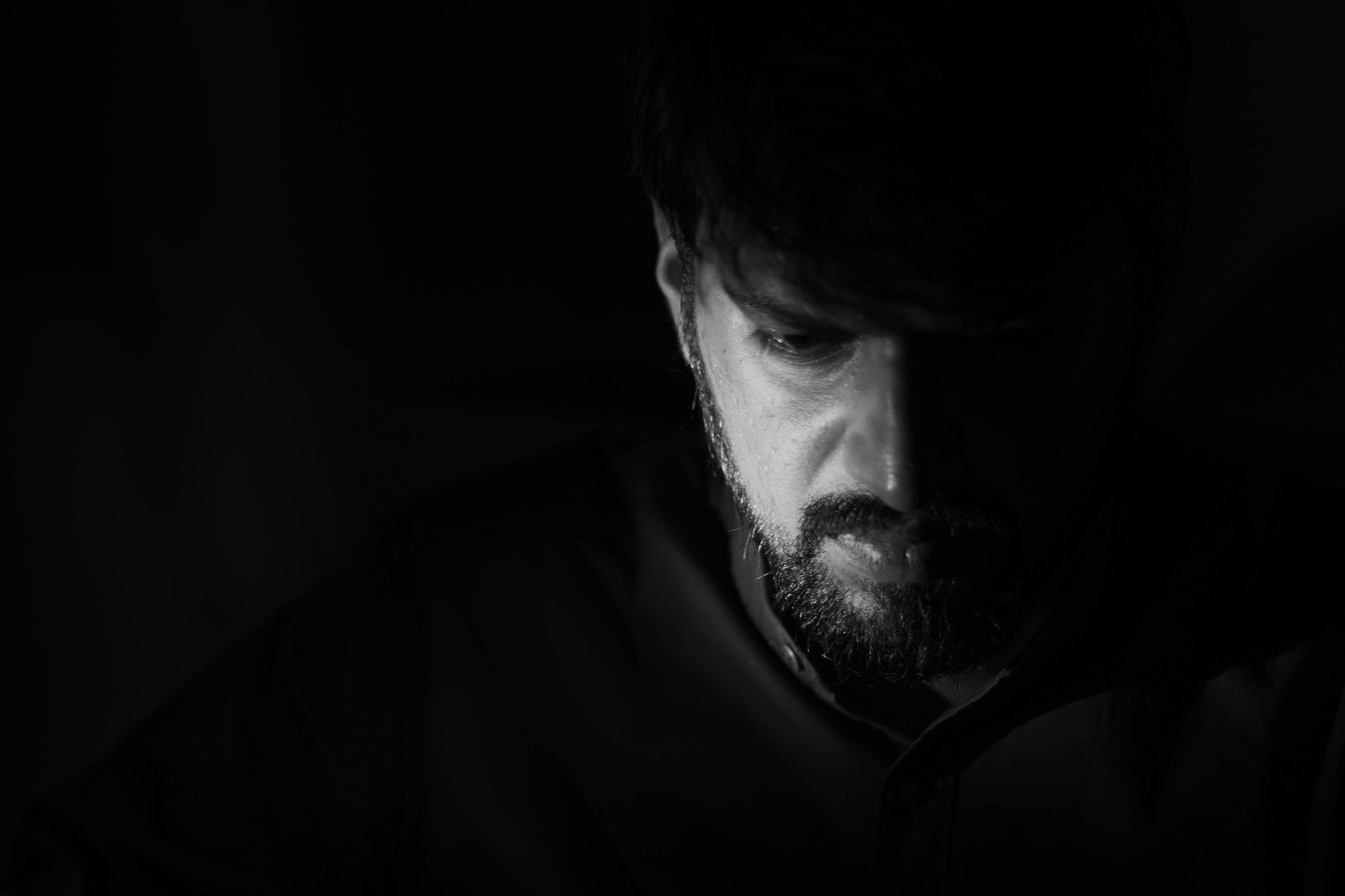 beard, facial hair, one person, black background, studio shot, headshot, indoors, men, males, portrait, close-up, mid adult men, front view, mid adult, adult, dark, lifestyles, young men, body part, human face, mustache, contemplation
