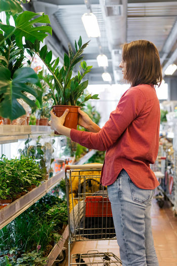 Midsection of woman standing by store buying plants