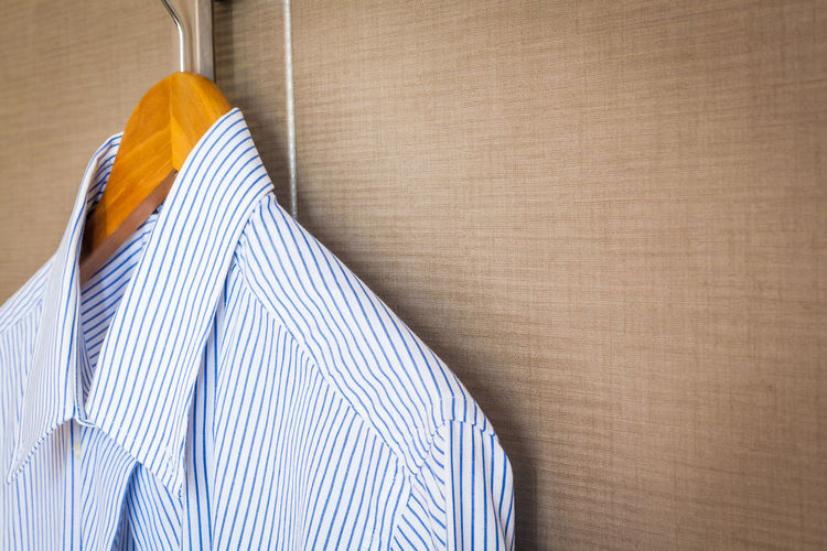 Close-up of blue shirt hanging on brown wall