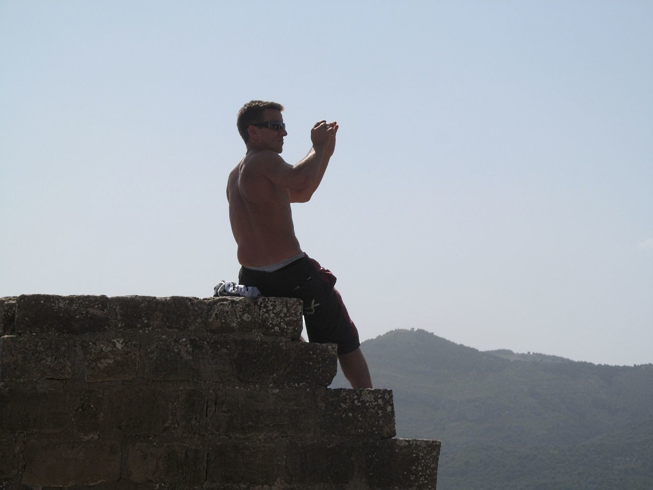 Low Angle View Of Shirtless Man Photographing By Mountains Against Sky
