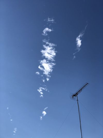 Low angle view of vapor trail against blue sky on sunny day