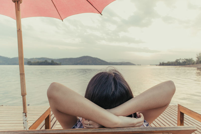 Midsection of woman sitting on wood against sky