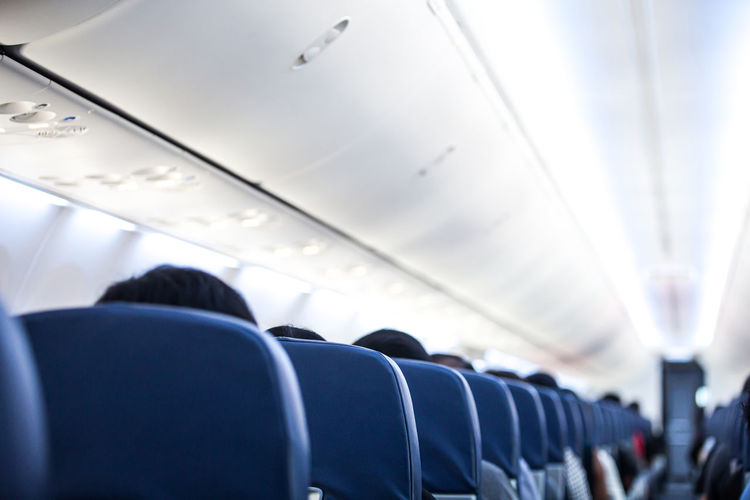 Rear view of man sitting in airplane