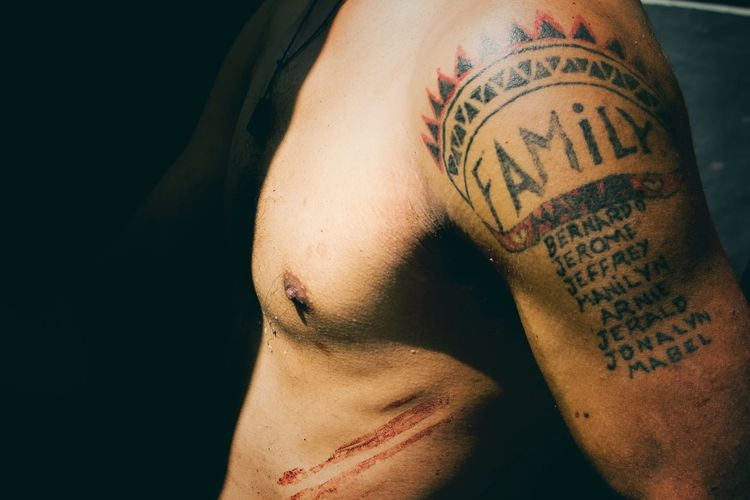 Midsection Of Shirtless Man With Tattoo On Arm