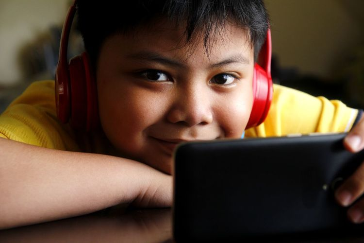 Asian boy with smartphone and headphones Digital Equipment Instrument Asian  Filipino Young Youth Kid Boy Male Headphone Earphones Stereo Audio Music Video MOVIE Cellphone Mobile Phone Smart Phone Web Surf Online  Electronics  Gadget Smile Happy Technology Child Internet