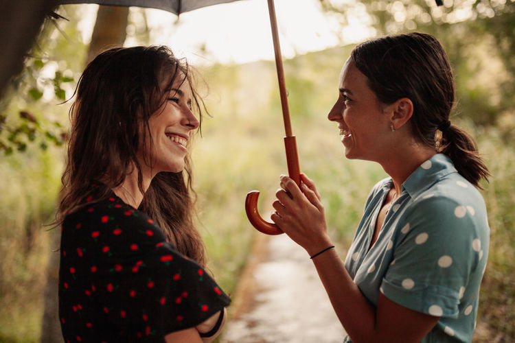 Side view of lesbian couple laughing while standing under umbrella