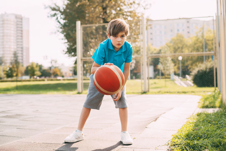 Focused cute boy athlete leads the ball in a game of basketball. a boy plays basketball after school