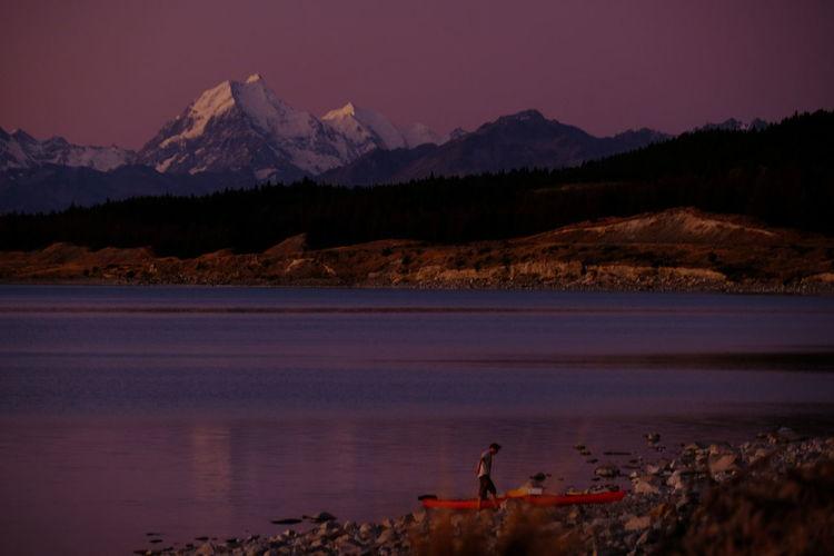 Man walking at lakeshore against mountains