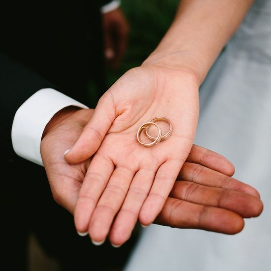 Close-up of hands holding wedding rings
