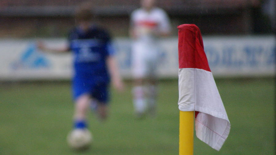 Close-Up Of Flag At Soccer Field With Players In Background