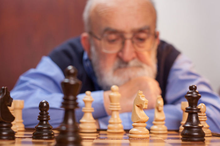 old man playing chess Blurred Losing Worried Challenge Checkmate Chess Chess Board Chess Piece Competitive Concentration Contemplation Decisions Eyeglasses  Intelligence Leisure Games Lifestyles Match Pensioner Player Playing Retirement Senior Adult Senior Men Skill  Strategy