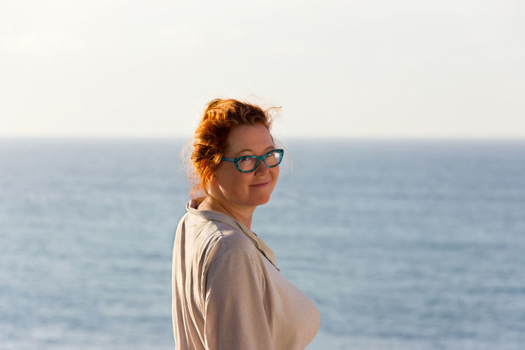 Adult Adults Only Beautiful Woman Day Eyeglasses  Horizon Over Water Leisure Activity Lifestyles Looking At Camera Nature One Person One Woman Only Only Women Outdoors Portrait Redhead Sea Side View Smiling Standing Sunlight Sunset Water Women Young Adult
