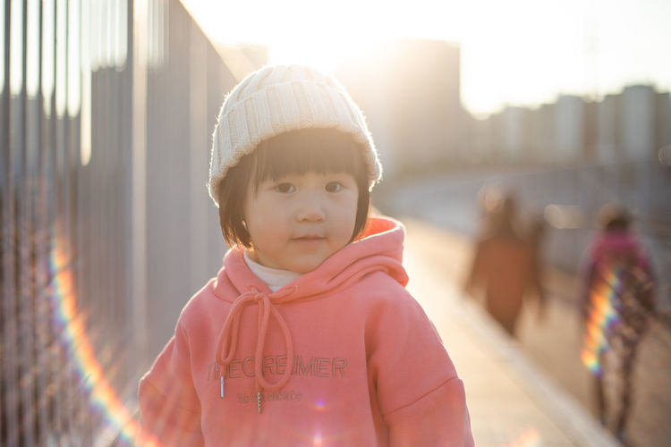 Portrait of cute girl standing against blurred background