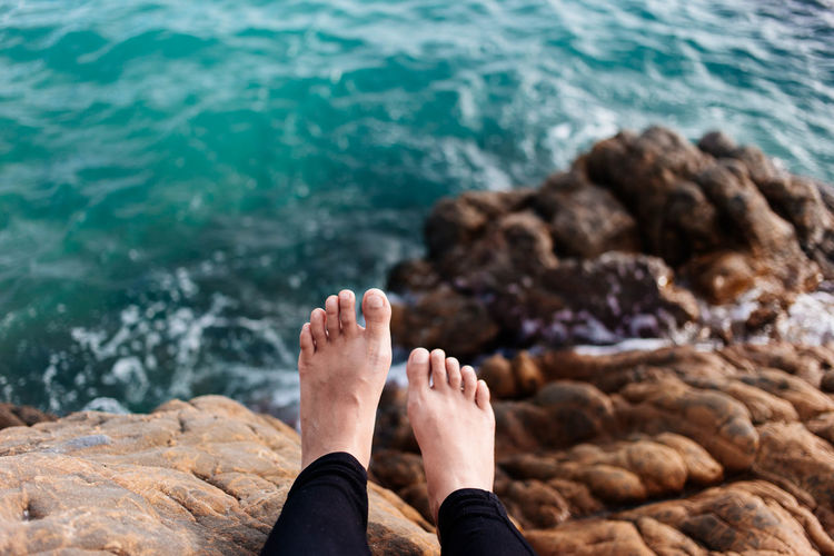 Young asian foots sitting at the stone of the beach in Thailand island. Feeling alone and relax. copy space for text quotes Alone Sitting Textured  barefoot Beach Beauty In Nature Coast Day Horizon Over Water Human Body Part Human Leg Island Leisure Activity Lifestyles Low Section Men Nature One Person Outdoors Real People Relaxation Rock - Object Sea Sunlight Water
