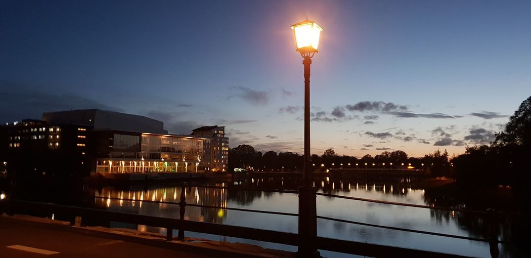 Illuminated street lights by lake against sky at night