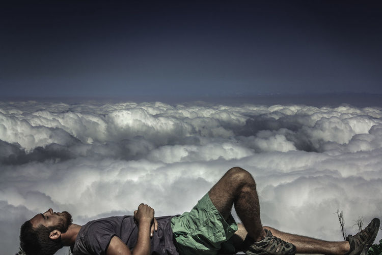 Side view of man lying on cliff by cloudy sky