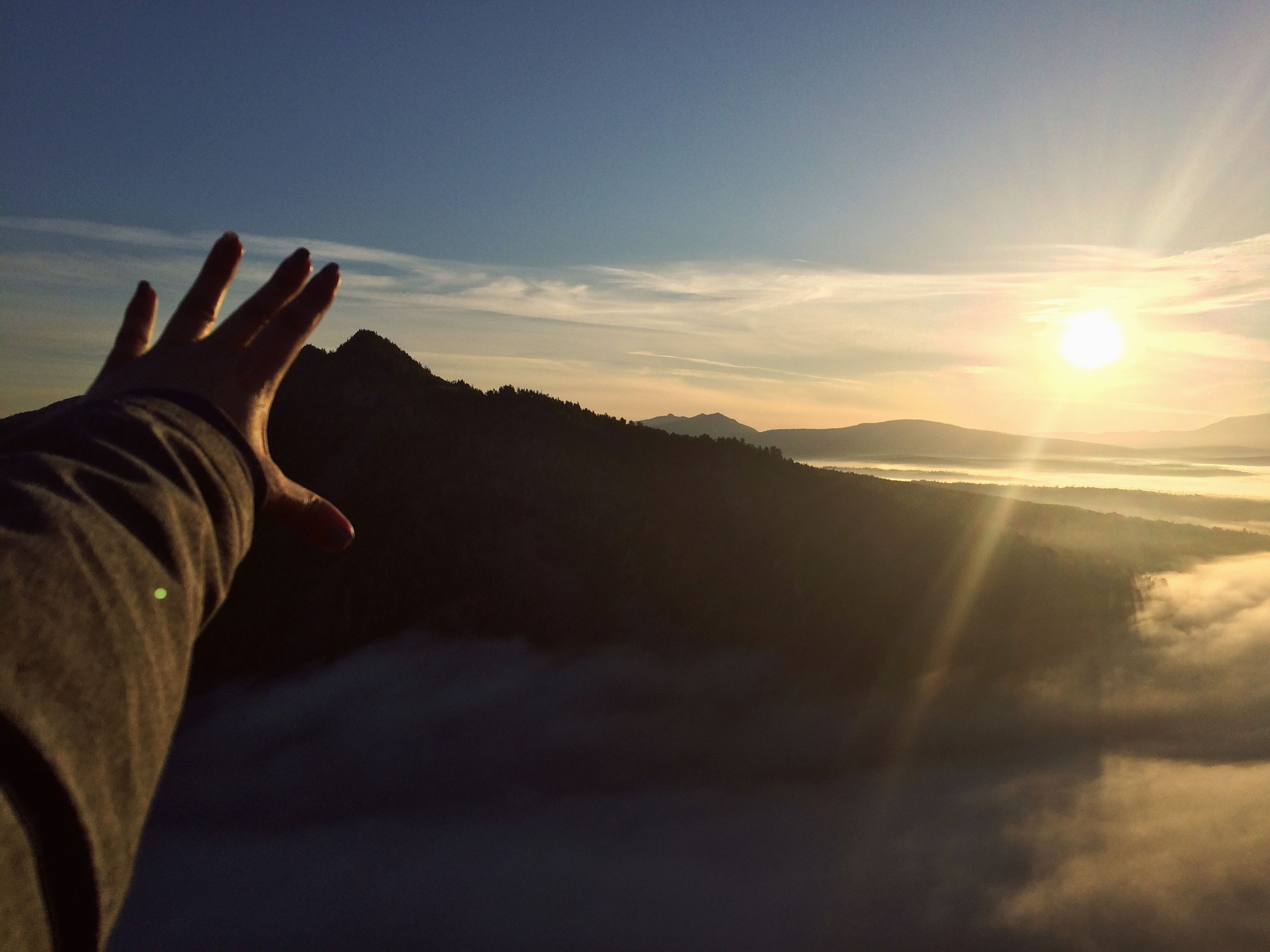 sky, sunset, cloud - sky, real people, sun, scenics - nature, one person, nature, beauty in nature, sunlight, mountain, human body part, hand, leisure activity, tranquility, human hand, tranquil scene, sunbeam, lens flare, body part, outdoors, finger, bright, human limb