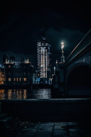 Illuminated queen elisabeth tower and big ben against sky at night from westminster bridge