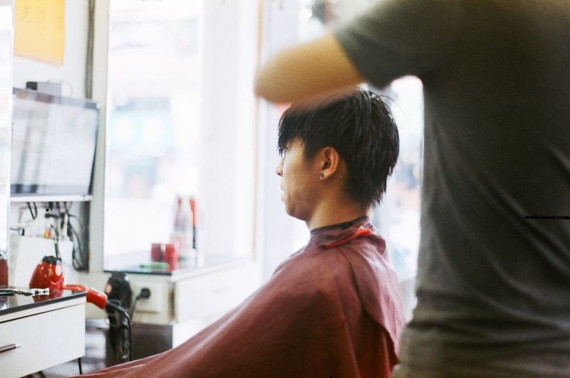 Barber cutting man hair at salon