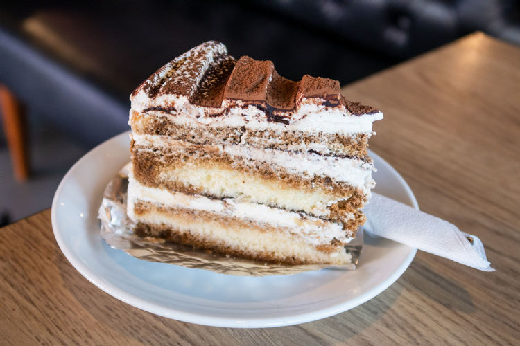 A piece of tiramisu cake on a white dish. traditional italian dessert