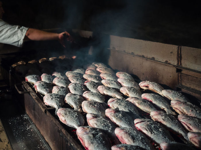 Cropped hand preparing fishes on barbecue grill