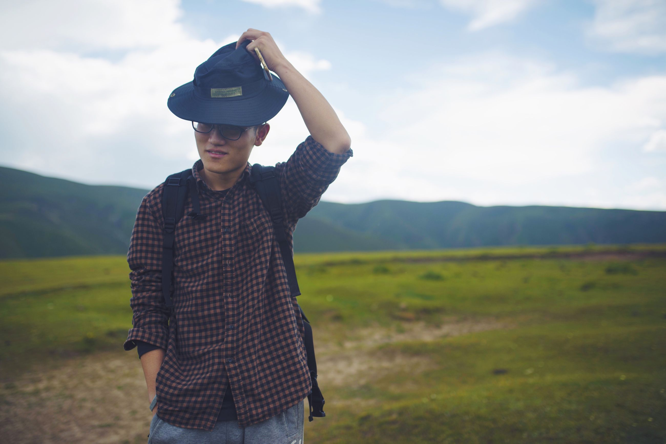 lifestyles, leisure activity, sky, casual clothing, landscape, young adult, person, field, cloud - sky, grass, three quarter length, standing, mountain, cloud, sunglasses, young men, front view, tranquility