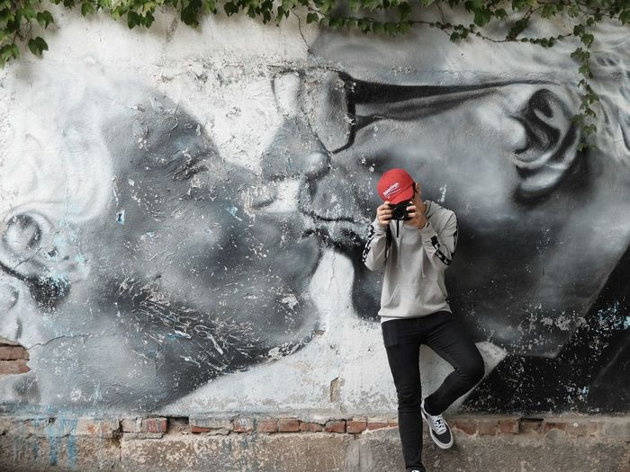Man Photographing Against Mural Wall