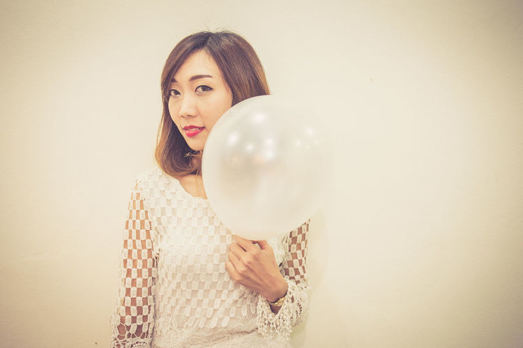 Portrait of woman with balloon standing against wall