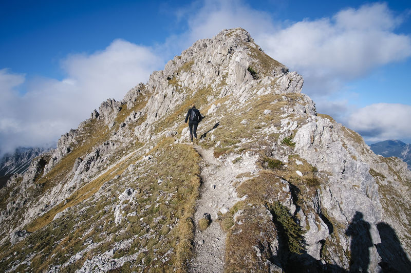 Rear view of woman walking on mountain ridge
