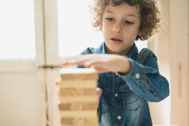 Caucasian kid is playing wood blocks tower game. Growing concept practicing intelligence skills. Growing Wood Blocks Boys Casual Clothing Child Childhood Curly Hair Day Front View Future Game Hairstyle Holding Indoors  Innocence Lifestyles Looking Males  Men One Person Real People Standing Vision Visonary Wood - Material
