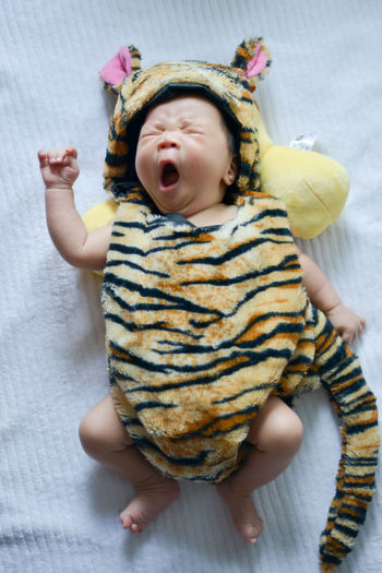 High angle view of baby in animal clothing yawning while lying on bed