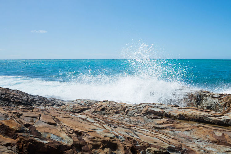 Waves splashing on rocks at shore against blue sky