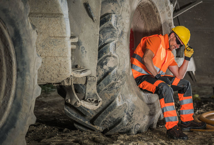 Manual worker sitting on truck tire