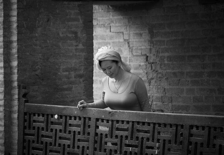 Woman wearing turban standing by railing