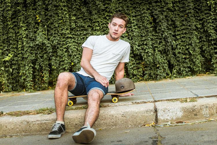 Full length portrait of man sitting on skateboard