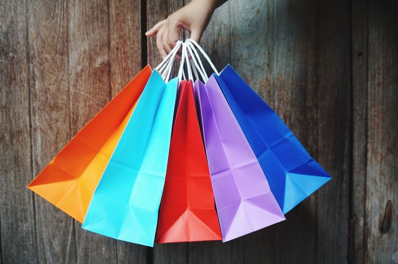 Cropped hand of person holding colorful shopping bags against wooden wall