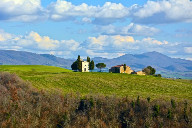 Farmhouses in field against cloudy sky