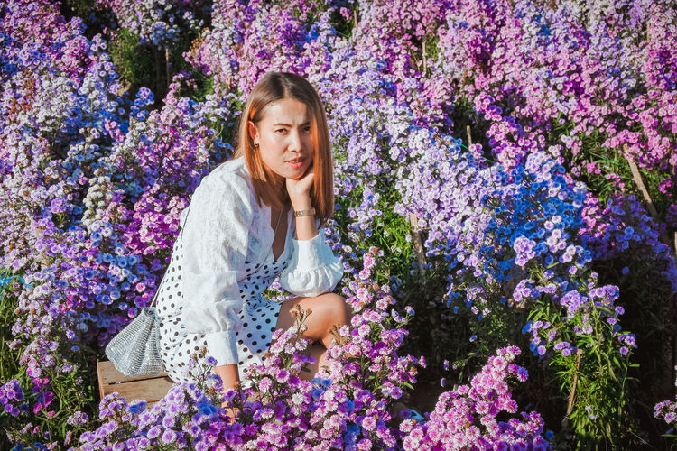 Young woman on purple flowering plants