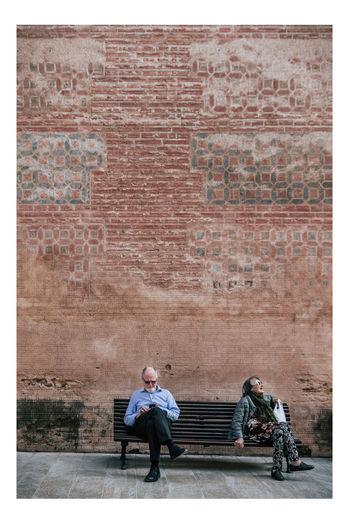 Man sitting on brick wall