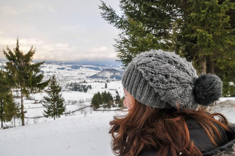 Rear view of woman on frozen tree against sky