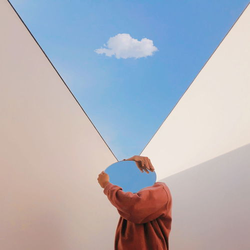 Person holding mirror against sky