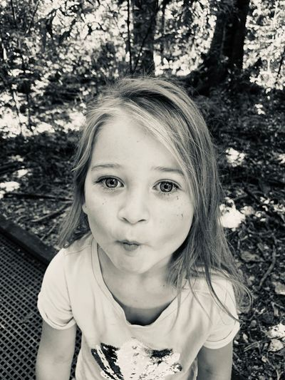 Portrait of girl pouting while standing in forest