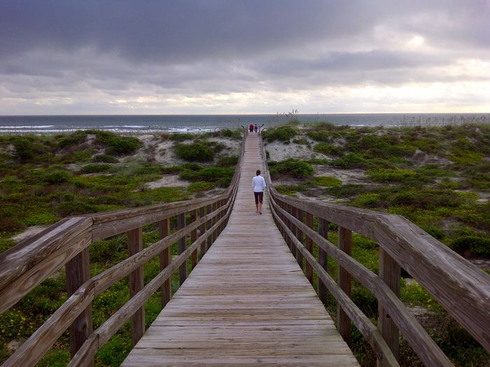Rear view of woman walking on pier leading towards sea against cloudy sky