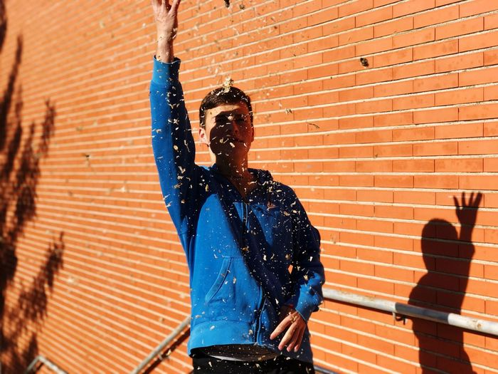 Young Man Throwing Dry Leaves While Standing Against Brick Wall