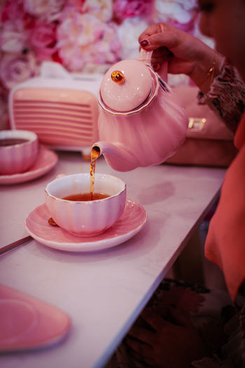 Person pouring tea cup on table